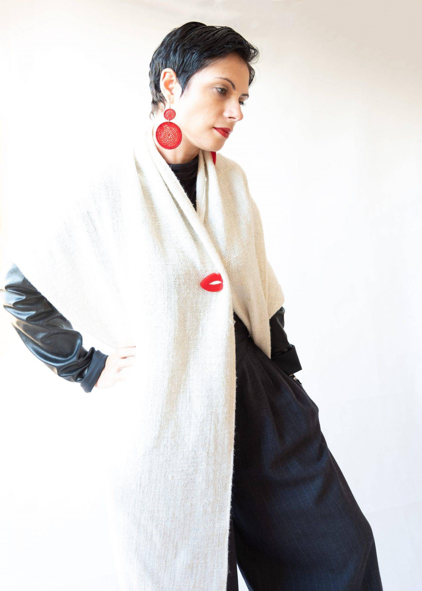 Outfit with dark grey culottes, white woollen cardigan, black turtleneck, red earrings and perspex lips brooch
