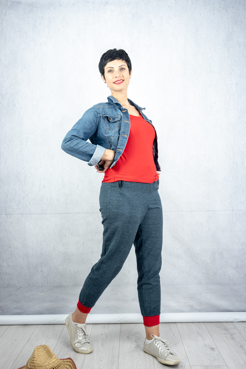 Grey joggers with red cuffs, worn with red t-shirt, denim cropped jacket and metallic grey trainers